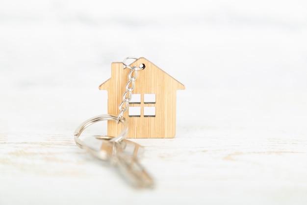 Uma chave em uma casa em forma de chaveiro de madeira