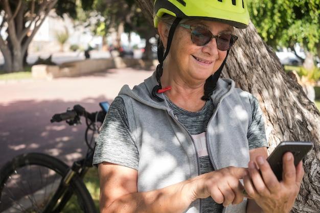 Uma ciclista com um capacete amarelo para no parque para usar um telefone celular. apoiada no tronco de uma grande planta, ela escreve uma mensagem em seu celular