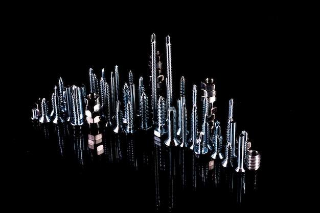 Uma cidade fantástica feita de parafusos, porcas, parafusos e auto-cortes em um fundo preto com reflexão