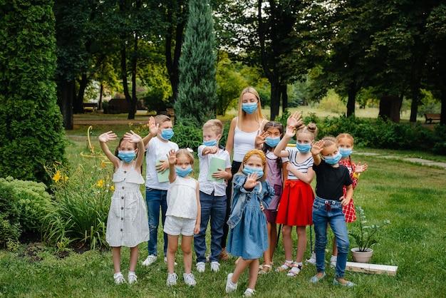 Uma classe de alunos mascarados está envolvida em treinamento ao ar livre durante a epidemia. de volta à escola, aprendendo durante a pandemia.
