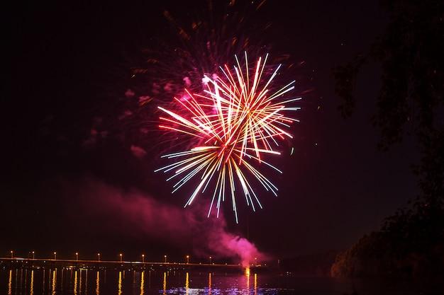 Uma colagem de fogos de artifício explodindo no meio da noite. decorado com pontos de luz. bom para o fundo do feriado.