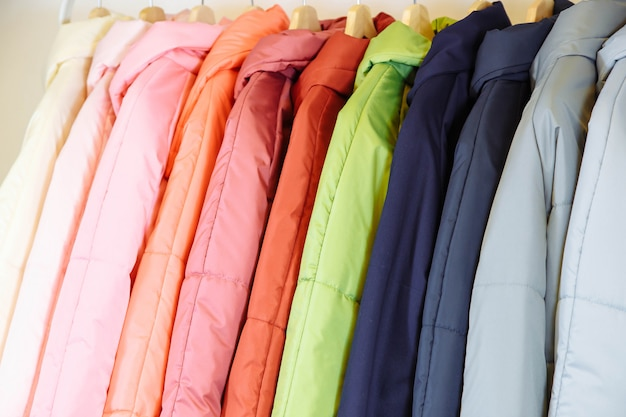 Uma coleção de elegantes casacos de outono em cabides na loja