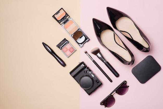 Uma coleção de maquiagem de beleza cosmética com câmera e sapatos em fundo de cor clara