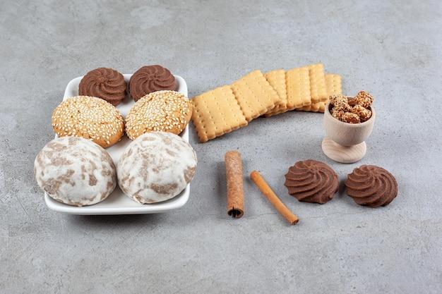 Uma coleção de vários biscoitos, biscoitos, cortes de canela e uma pequena tigela de amendoim glaceado na superfície de mármore.
