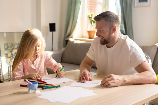 Uma colegial do ensino fundamental e o pai desenhando juntos com lápis de cor enquanto ficam em casa para a quarentena