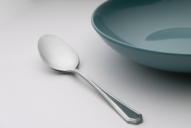 Uma colher ao lado de um prato azul sobre uma mesa