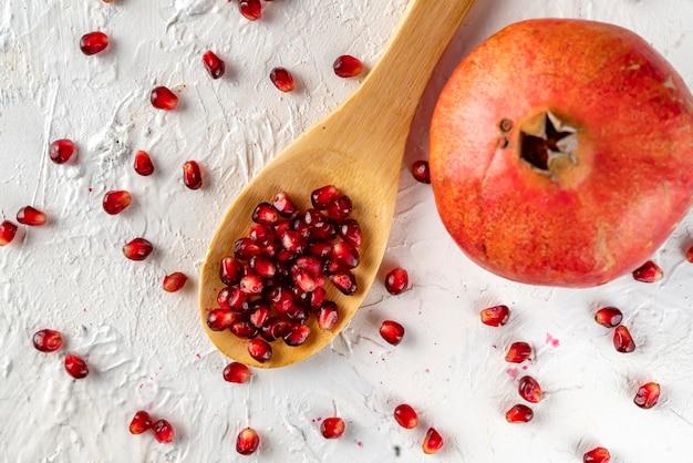 Uma colher com frutas romã plana leigos com sementes e grãos na mesa plana coloca