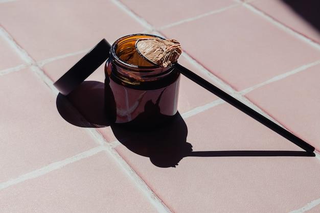 Uma colher com máscara de argila facial ao lado de um frasco de produto cosmético de vidro marrom em um banheiro de azulejos rosa