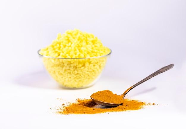 Uma colher de açafrão é espalhada sobre uma mesa branca, com arroz