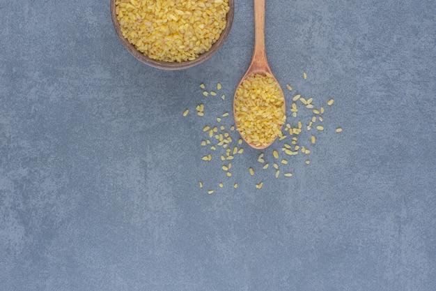 Uma colher de arroz e uma tigela de arroz, no fundo de mármore.