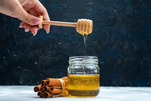 Uma colher de imersão feminina de mel e canela, vista frontal, no mel na planta de açúcar de fundo azul-cinza