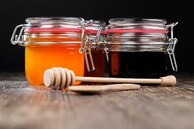 Uma colher de mel junto com mel de abelha de alta qualidade, uma mesa velha na qual há um mel de abelha saudável e doce e uma colher de madeira caseira que permite transferir e despejar o mel