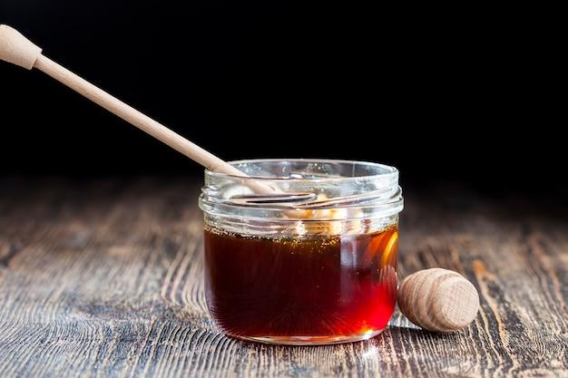Uma colher de mel junto com mel de abelha de alta qualidade, uma mesa velha na qual há um mel de abelha saudável e doce e uma colher especial de madeira