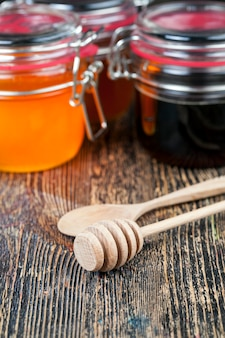 Uma colher de mel junto com mel de abelha de alta qualidade uma mesa velha na qual há um ...