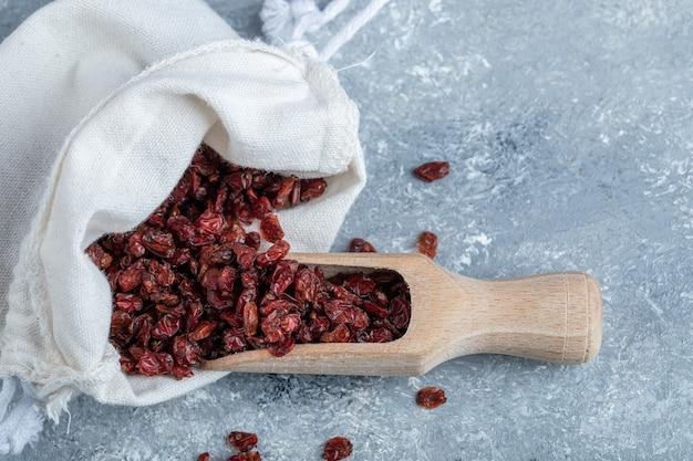 Uma colher de pau cheia de cranberries secas na superfície de mármore.