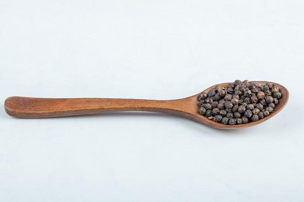 Uma colher de pau cheia de pimenta seca em um fundo branco.