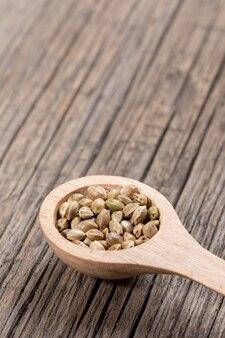 Uma colher de pau com sementes de maconha em placas de madeira velhas diagonais.