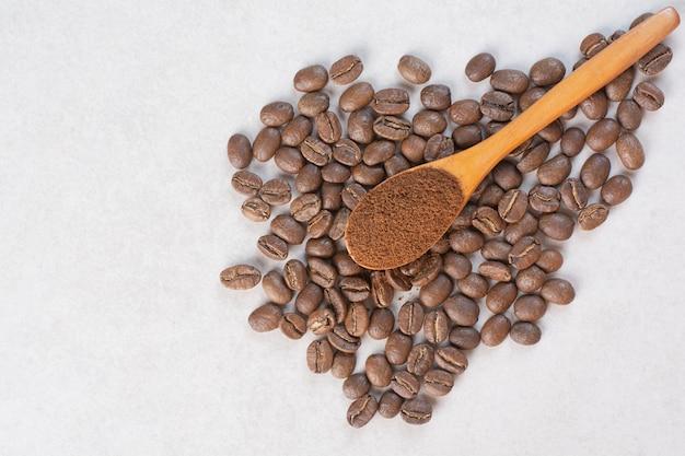 Uma colher de pau de cacau em pó com grãos de café. foto de alta qualidade