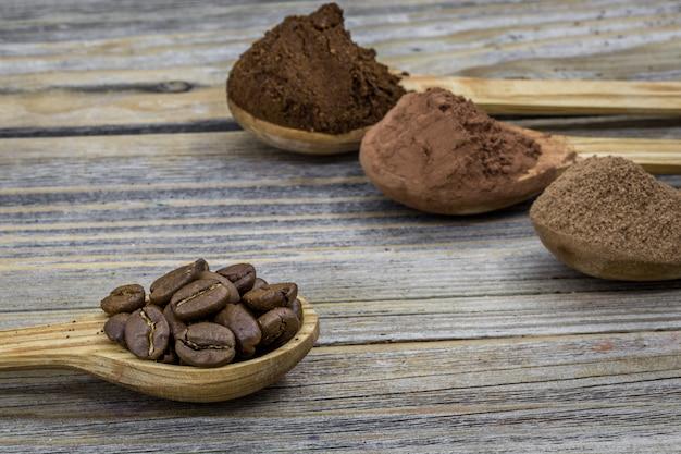 Uma colher de pau pequena bonita com café em madeira ângulo diferente, closeup