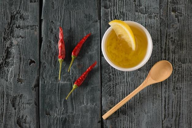 Uma colher de pau pequena e uma xícara de azeite e alho e três pimentas em uma mesa de madeira preta. molho para salada de dieta