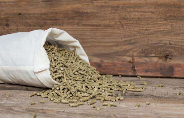 Uma colher derramada com pellets para coelhos à venda na forragem