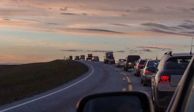 Uma coluna de carros em uma estrada sinuosa no fundo das montanhas e do mar ao pôr do sol