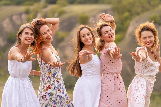 Uma companhia alegre de amigas lindas desfruta da companhia e se diverte em um lugar pitoresco de colinas verdes.