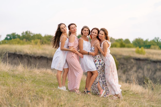 Uma companhia alegre de lindas amigas desfruta da companhia e se diverte em um lugar pitoresco de colinas verdes.