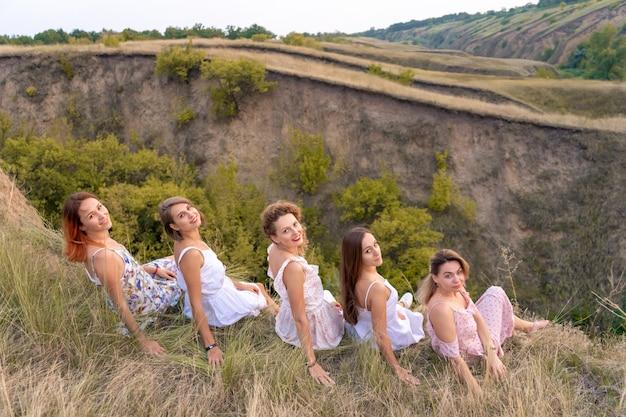 Uma companhia alegre dos amigos da mulher desfruta de uma paisagem pitoresca das colinas verdes ao pôr do sol
