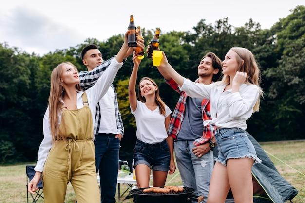 Uma companhia de amigos levantando uma garrafa com uma cerveja no acampamento. - imagem