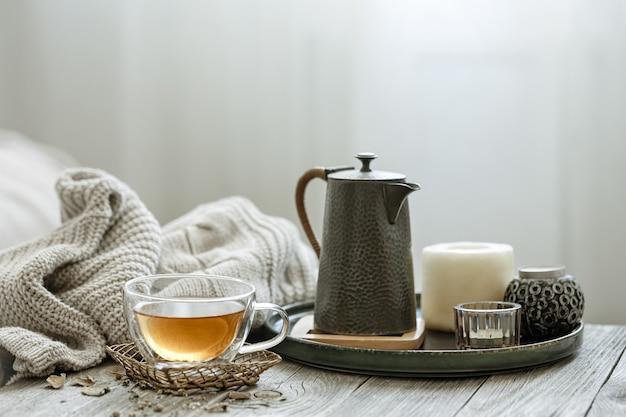 Uma composição aconchegante com uma xícara de chá, uma vela no interior da sala em um fundo desfocado.