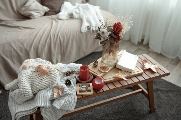 Uma composição caseira aconchegante com velas e um livro de blusas de malha