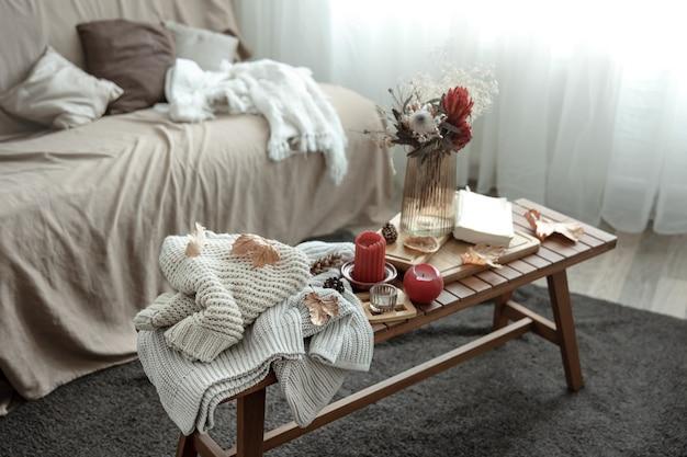 Uma composição caseira aconchegante com velas, um livro, blusas de malha e folhas
