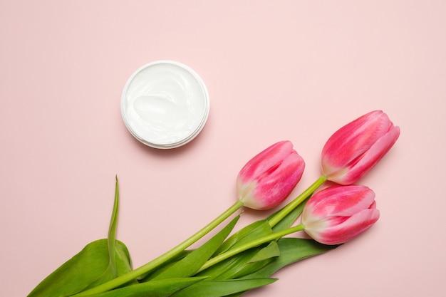Uma composição com tulipas e um pote de creme para as mãos em um fundo rosa.