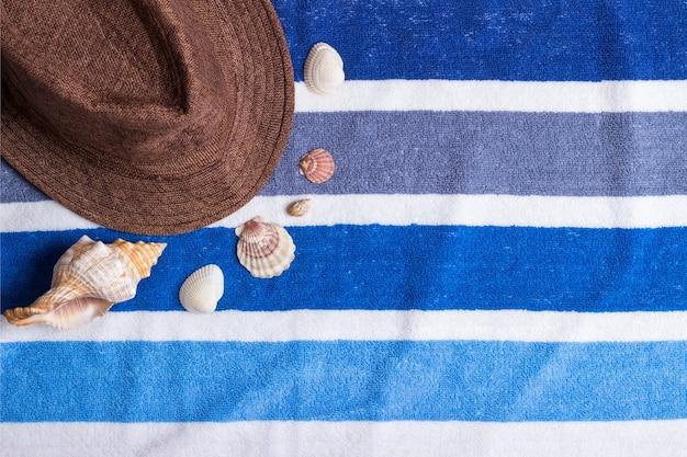Uma composição de férias de verão em uma toalha de praia com conchas e um chapéu.