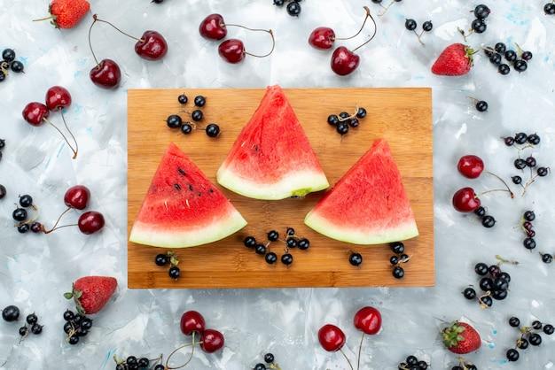 Uma composição de frutas em fatias de melancia junto com frutas frescas em branco, cor de fruta suave