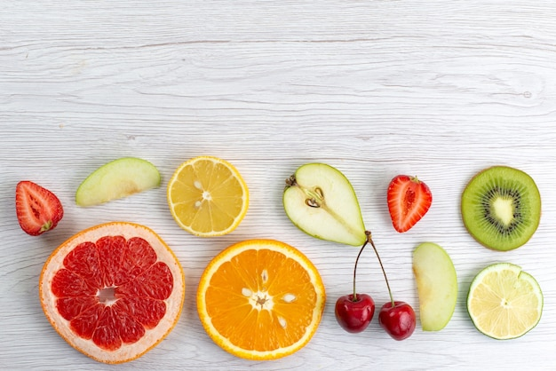 Uma composição de frutas frescas cortadas em fatias maduras e suculentas em branco, foto colorida de frutas maduras
