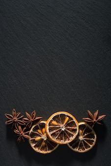 Uma composição de limões secos e anis em ardósia natural