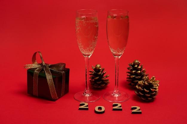 Uma composição de objeto de ano novo, numerais de madeira 2022, pinhas douradas, presente de natal em papel de embrulho glitter com laço dourado, taças de champanhe com espumante em fundo vermelho, espaço de cópia