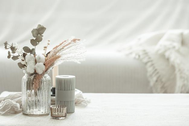 Uma composição minimalista no estilo escandinavo com flores secas em um vaso e velas.