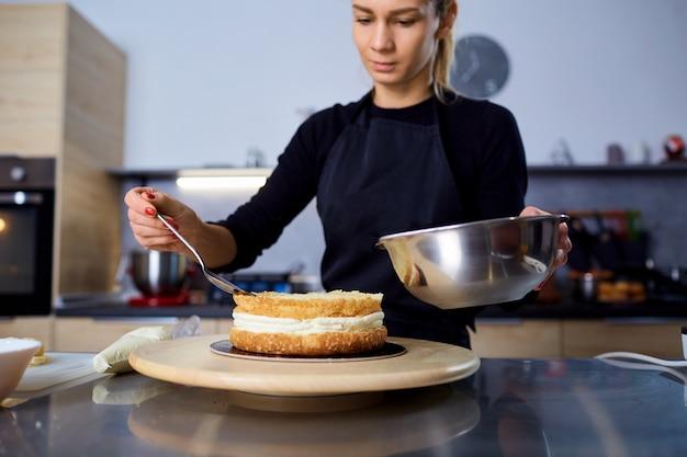 Uma confeiteira faz bolo na cozinha de uma confeitaria.
