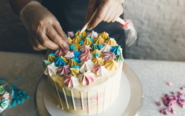 Uma confeiteira faz um bolo de casamento com as próprias mãos e coloca decorações coloridas nos bolos com creme