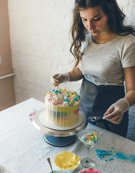 Uma confeiteira faz um bolo de casamento com as próprias mãos e põe enfeites coloridos com creme nos bolos. preparação para a celebração.