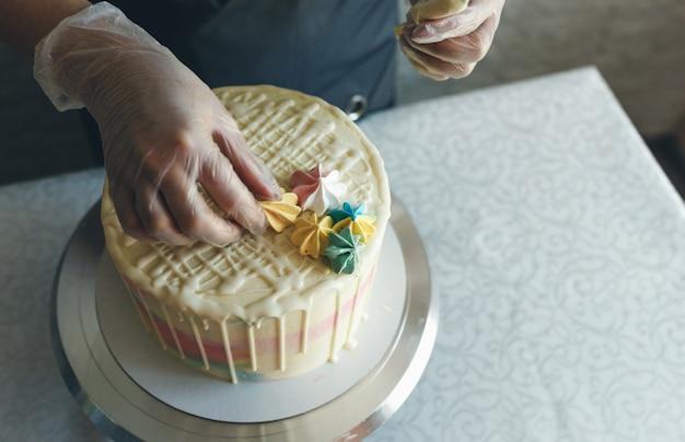 Uma confeiteira faz um bolo de casamento com as próprias mãos