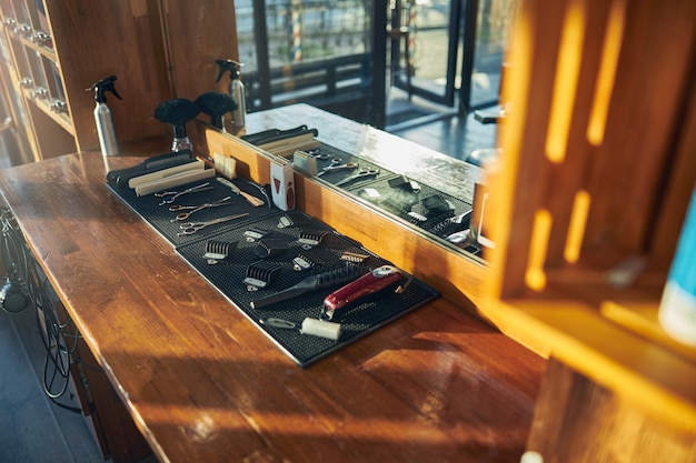 Uma configuração minimalista de diferentes ferramentas de barbearia sobre uma mesa de madeira limpa
