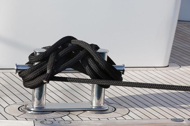 Uma corda de amarração com uma extremidade com nós amarrada em torno de um grampo em um píer de madeira