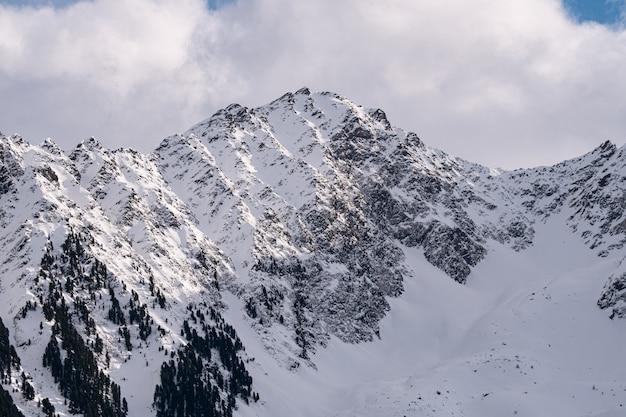 Uma cordilheira alpina íngreme coberta de neve