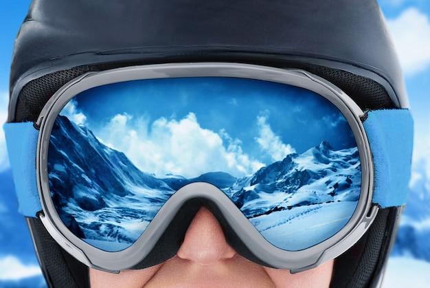 Uma cordilheira refletida na máscara de esqui. menina usando máscara de esqui