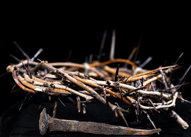 Uma coroa de espinhos e um prego enferrujado jazem no escuro. o conceito de semana santa e a crucificação de jesus.