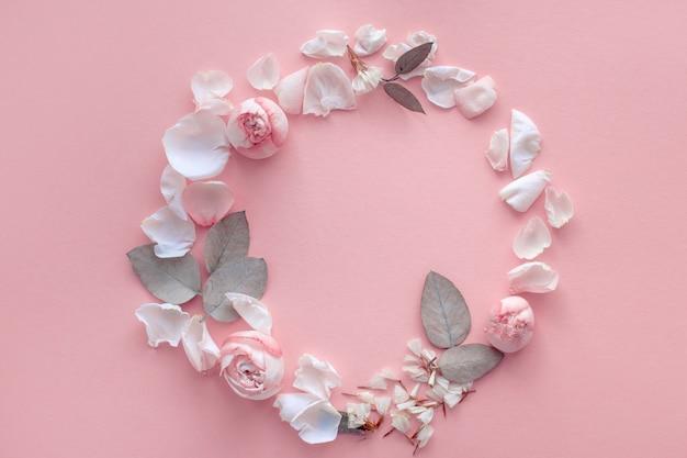 Uma coroa de flores e pétalas de rosa em um fundo rosa suave